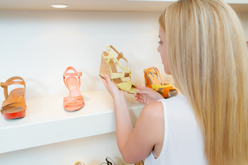 Lady looking at sandals in shoe shop