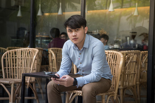 Southeast asian young businessman holding mobile phone and looking camera at outside coffee shop