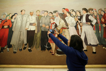 A journalist takes photos of a painting depicting the late Chinese Chairman Mao Zedong, at a group discussion session during China's National People's Congress in Beijing