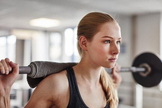 Junge Frau trainiert konzentriert Kniebeugen