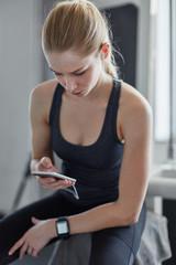 Junge Frau liest eine SMS im Fitnesscenter