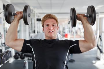 Bodybuilding Mann trainiert mit Kurzhanteln