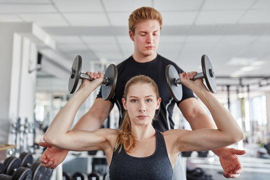 Trainer hilft junger Frau beim Hanteltraining