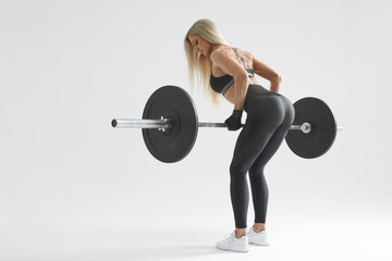 Photo of confident young woman doing weight lifting workout at gym turning back Attractive young woman bodybuilder lifting barbells looking focused