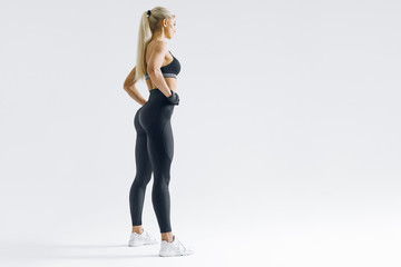 Full length portrait of fitness woman standing with her arms on hips Female model in sportswear...