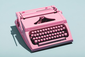 Pink typewriter on a blue pastel background.