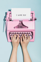 "Woman's hands writing ""I love you"" on a typewriter."