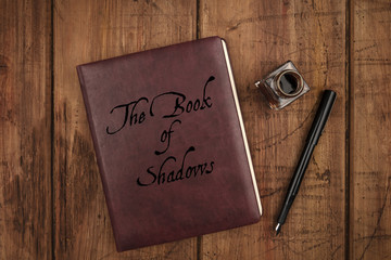 Leather bound journal titled The Book of Shadows, a witch's grimoire, and ink well and pen