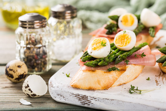 Fresh sendwich with ham, asparagus and quail eggs on white old chopping board on wooden background. Easter spring breakfast concept.