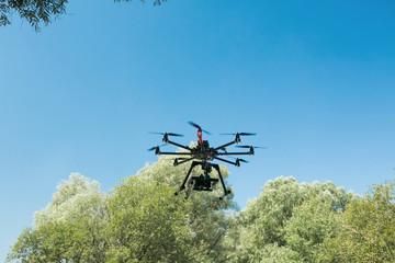 Unmanned aircraft in black, flying with a digital camera. Demon with a digital camera of high resolution. The flying camera takes photos and video. Dron with a professional camera takes pictures of