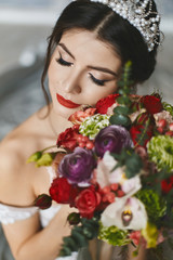 Young beautiful and sexy brunette woman, in white dress and diadem on her head, with flowers in her hands