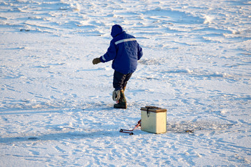 A man on ice is fishing in the evening