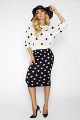 Beautiful, sexy blonde woman in elegant clothes in polka dots and a hat