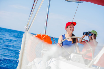 Boy captain with his sister on board of sailing yacht on summer cruise. Travel adventure, yachting with child on family vacation.