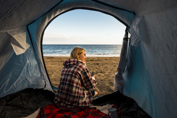 lifestyle for blonde beaitufl woman outside her tent near the ocean