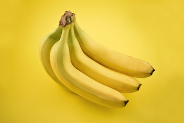 Banana stock images. Banana on a yellow background. Bunch of ripe bananas