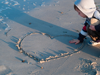 child by the sea heart drawn in the sand touches it with his hand