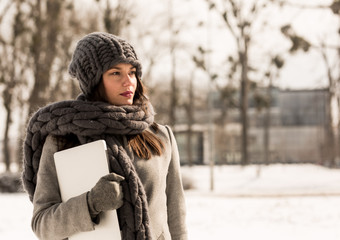 Serious woman with laptop in winter forest