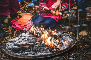 Open barbecue fireplace outside in the autumn season.. Roasting swiss sausages called in German Cervelat and Bratwurst.