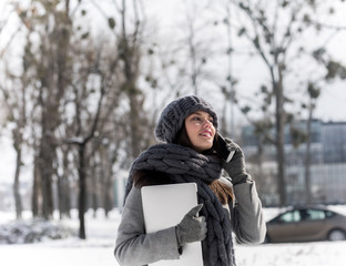 Using smartphone and holding laptop outdoors in winter