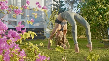 Professional performance of asana yoga by a young girl at backyard of her house