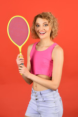 Tennis player, stylish girl holding tennis racket. Playing tennis is fun. Sport is good for health. Sport, game, active lifestyle concept - woman player with tennis racket isolated on red background.