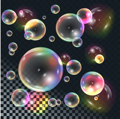 Soap transparent bubbles with rainbow reflection on dark checkered background.