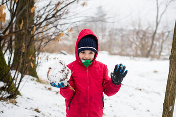 portrait of child with red jacket and hat in the snowy forest, in hands holds a big snowball
