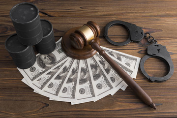 barrels of oil, dollars, handcuffs, judge's hammer on a wooden background. illegal mining of raw materials.