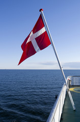 Dannebrog: The Danish national flag is fluttering in the wind at the stern of a small ferryboat crossing the Kattegat Sea