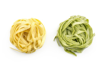 Fettuccine pasta raw (one spinach and classic) top view isolated on white background two pieces.