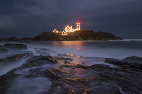 Holiday lights at Nubble Lighthouse in Maine during high tide