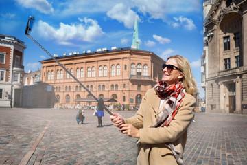 Happy old senior blonde woman take selfie on smartphone - spring street old city