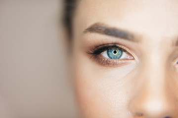 Close-up shot of beautiful blue eye of the attractive fresh woman with natural make-up at beige background. Part of healthy face. Wall mural