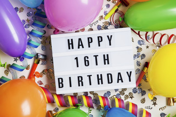 Happy 16th birthday celebration message on a lightbox with balloons and confetti