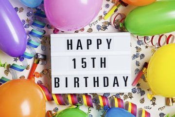 Happy 15th birthday celebration message on a lightbox with balloons and confetti