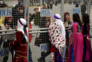 Participants stand behind security barriers during a rally on the International Women's Day in Diyarbakir