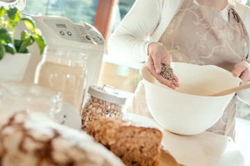 Woman in the kitchen pours sunflower seeds into a bowl with bread dough