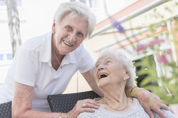 Two senior women laughing at nursing home