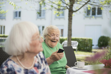 Senior woman laughing and using smartphone