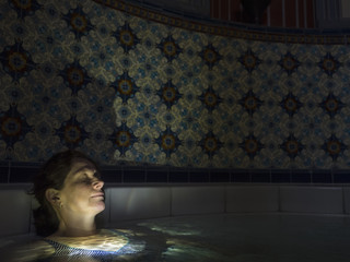 Woman relaxing in swimming pool of Palais-Thermal of Bad Wildbad, Baden-Württemberg, Germany