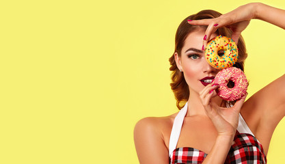Beautiful young bright girl in retro style holds two bright donut in hands.Fashion, beauty, makeup, retro, pin-up, cosmetics, dessert, delicious, advertising, bright, magazine, postcard, hairdo.