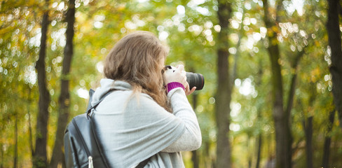 woman with photo camera in autumn forest