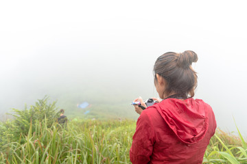 Traveller standing and take photo on a hill in the morning with foggy view and rain