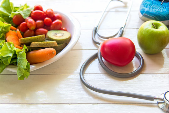 Diet and weight loss for healthy care with medical stethoscope, fitness equipment, vegetable salad and healthy food with red heart on the old white wooden background top view. Healthy Concept.