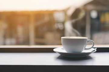 Coffee cup on the table and window background