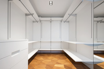 Large white walk-in closet with parquet