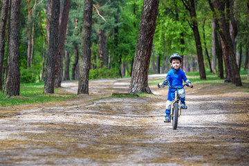 Happy cute blond kid boy having fun his first bike on sunny summer day, outdoors. Happy child making sports. Active leisure for children.Kid boy wear safety helmet. boy is smiling and cicling.