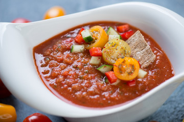 Close-up of cold spanish gazpacho soup served in a white bowl, selective focus