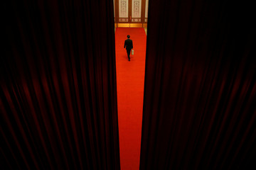 Attendant is seen between curtains during the second plenary session of the CPPCC at the Great Hall of the People in Beijing